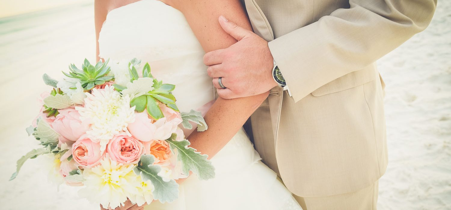 Bride and Groom with a bouquet of flowers on the white sandy beaches of Northwest Florida